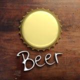在木背景隔绝的金黄金属啤酒盖帽,在银色信件的文本啤酒,顶视图 3d例证 库存照片