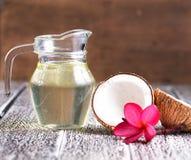 在木背景隔绝的椰子油 免版税库存照片