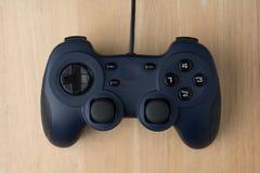 在木背景顶视图的电子游戏控制器 免版税库存照片