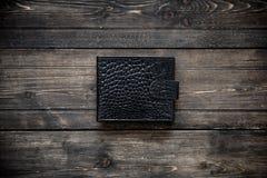 在木背景顶视图的黑暗的皮革钱包 图库摄影