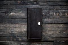在木背景顶视图的黑暗的皮革钱包 免版税库存图片