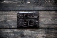 在木背景顶视图的黑暗的皮革钱包 免版税库存照片