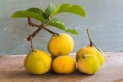 在木背景,与绿色leaf的黄色santol的Santol果子 免版税图库摄影