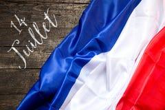 在木背景,概念7月14日的法国旗子 库存照片