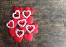 在木背景,爱骗局的情人节红色和桃红色心脏 免版税图库摄影