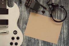 在木背景,纸片的电吉他,耳机,加速传动装置影响脚蹬 免版税库存照片