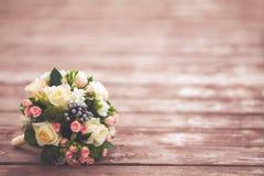 在木背景,被定调子的葡萄酒的美丽的婚礼花束 免版税库存照片