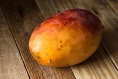在木背景,选择聚焦的成熟五颜六色的芒果 库存照片