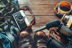在木背景,顶视图的旅行辅助部件 老远足的皮靴、背包、葡萄酒影片照相机和刀子 库存照片