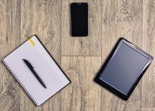 在木背景,顶视图,笔,智能手机,片剂的小配件 库存图片