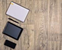 在木背景,顶视图,笔,智能手机,片剂的小配件 免版税图库摄影