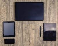 在木背景,顶视图,膝上型计算机,智能手机,片剂,笔的小配件 库存照片
