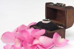 在木胸口的定婚戒指与桃红色玫瑰花瓣 免版税库存照片