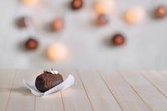 在木自然本底的鲜美巧克力蛋糕 用奶油和果冻片断装饰的顶面  在背景焕发圆的l 库存照片