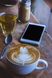 在木葡萄酒桌上的咖啡热的饮料cappucino拿铁艺术,在木背景咖啡馆的咖啡时间 免版税库存图片