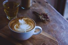 在木葡萄酒桌上的咖啡热的饮料cappucino拿铁艺术,在木背景咖啡馆的咖啡时间 免版税库存照片