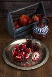 在木葡萄酒背景的成熟石榴果子 在黑暗的背景的红色汁液石榴 新鲜的水多的石榴- 库存照片