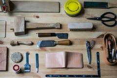 在木表上的皮革装璜工具 库存照片