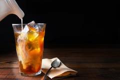 在木表上的被冰的咖啡与匙子 库存图片