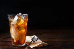 在木表上的被冰的咖啡与匙子 免版税库存图片