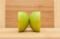 在木表上的被对分的绿色苹果计算机 库存图片