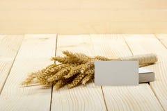 在木表上的麦子耳朵与空白的名片 捆在木背景的麦子 收获概念 库存照片