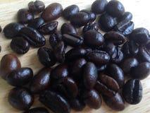 在木表的咖啡种子 免版税库存图片