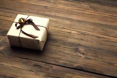在木表,被包裹的葡萄酒纸上的礼物盒当前与弓 免版税库存图片