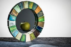 在木被定调子的框架纹理的手工制造镜子崩裂了油漆用反射在桌上的绿色苹果 库存照片
