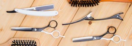 在木轻的背景、一套为切开的工具,剪刀,梳子上和 免版税库存照片