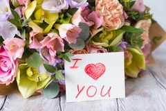 在木轻的背景的淡色花束与标记 我lo 库存图片