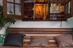 在木长凳的棕色枕头在开窗口旁边 库存照片