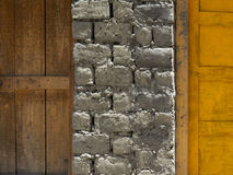 在木门之间的一个砖墙:在左边是一个老棕色门,在右边是一个明亮的黄色门,一块现代石头和 免版税库存照片