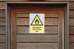 在木门的危险易燃气体警告小心标志 免版税库存照片