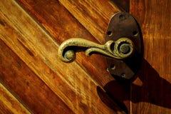 在木门的老古铜色把柄 免版税库存照片