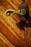 在木门的老古铜色把柄 免版税库存图片