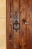 在木门的金属生锈的圆的把柄 免版税库存照片