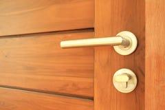 在木门的门把手 免版税库存照片