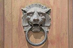 在木门背景的大狮子头通道门环 免版税库存照片