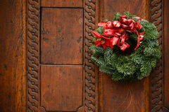 在木门装饰的圣诞节花圈 库存照片