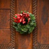 在木门装饰的圣诞节花圈 库存图片
