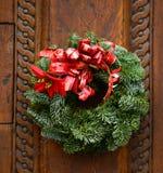 在木门装饰的圣诞节花圈 免版税图库摄影