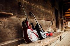 在木门廊的吉他 免版税库存照片