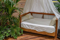 在木门廊的有四根帐杆的卧床床 免版税图库摄影
