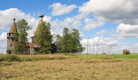 在木附近的古老教会割晒牧草 免版税库存图片