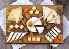在木面包板的各种各样的乳酪 免版税库存图片