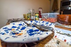 在木饭桌上吃的食物以后倒空有叉子匙子和刀子的使用的五颜六色的板材 免版税图库摄影