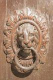在木头和古铜的敲门人 库存照片