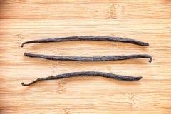 在木头排列的三香草荚 免版税库存照片
