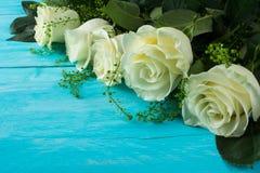 在木绿松石背景的象牙玫瑰 库存照片